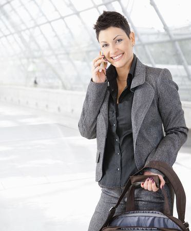 Young businesswoman talking on mobile phone on office lounge, smiling. Stock Photo - 5758821