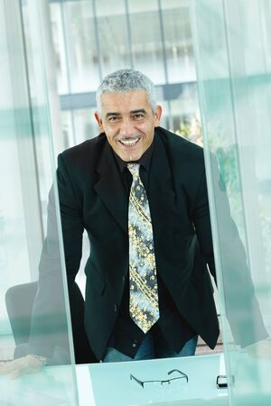 Nature businessman standing leaning to desk in modern glass office, smiling. photo