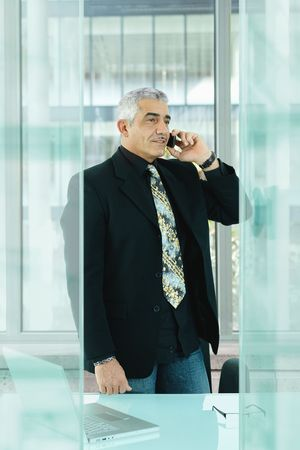 Nature businessman standing behind desk in modern glass office, talking on mobile phone. photo
