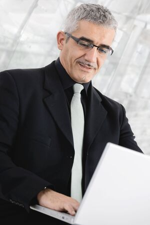 Closeup portrait of mature businessman  using laptop computer in front of office lobby windows. photo