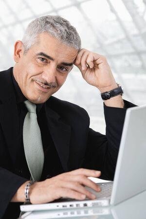 Closeup portrait of mature businessman sitting at desk, using laptop computer, smiling. photo