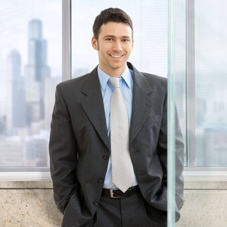 Portrait of businessman standing with hands in pocket in front of office windows, smiling. photo