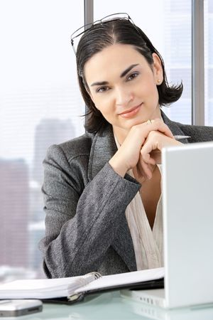 Businesswoman sitting at desk in front of offive windows, thinking over personal organizer. photo