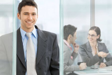 Happy businessman standing in modern glass office, businesswomen sitting at desk in the background, talking. photo