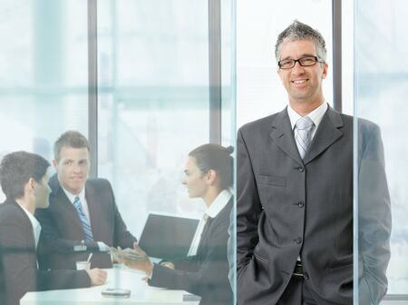 Happy businessman standing in modern glass office, businesspeople having a meeting in the background. photo