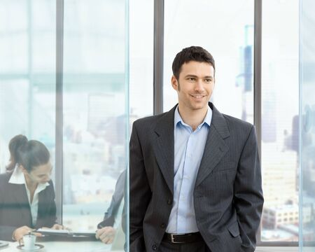 Happy businessman standing in modern glass office, businesswoman sitting at desk in the background, looking at personal organizer. photo