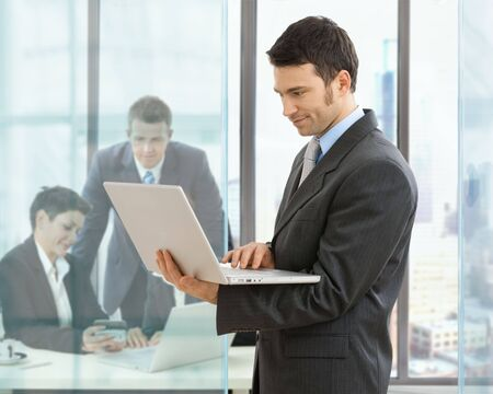 Businessman using laptop standing in office, businesspeople working at desk in the background. photo