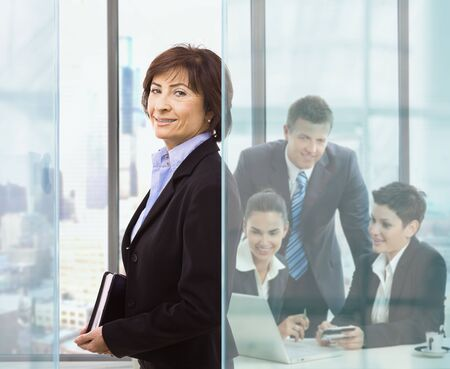 undoubting: Senior businesswomanstanding in office holding personal organizer. Businesspeople working at desk in background.