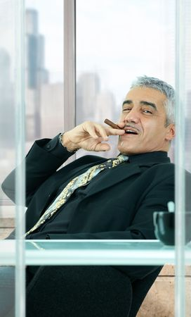 Confident businessman sitting at desk in front of office windows, leaning back, smoking cigar. photo