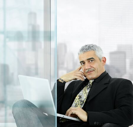 Portrait of mature businessman sitting  in front of windows in office, using laptop computer, smiling. photo