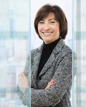blue grey coat: Senior businesswoman standing with arms crossed in front of office windows, smiling.