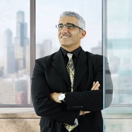 Confident businessman standing with arms crossed in front of office windows, smiling. photo