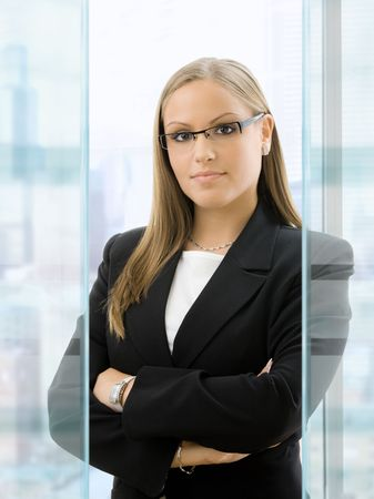 woman wearing glasses: Young businesswoman standing with arms crossed in front of office windows, smiling.