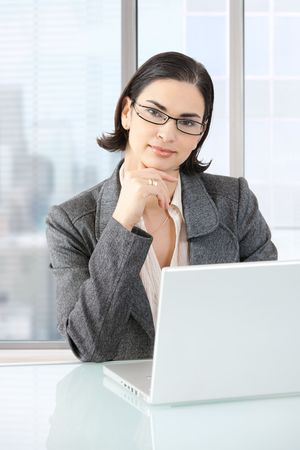 Businesswoman sitting at desk in front of offive windows, thinking over laptop computer. photo