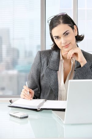 Businesswoman sitting at desk in front of offive windows, thinking over laptop computer and personal organizer. photo
