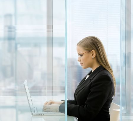 Young businesswoman sitting at desk in front of windows in modern office, using laptop computer. photo