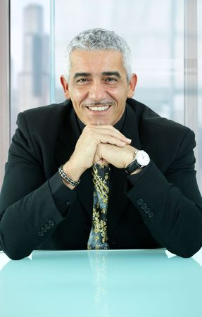 one mature man only: Portrait of casual businessman, sitting at desk in front of office windows, leaning on hands, smiling.