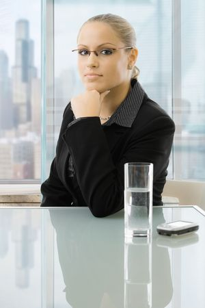 blond brown: Young businesswoman sitting at desk in front of windows, thinking leaning on hand.