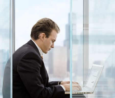 Profile portrait of businessman sitting in front of office windows, using laptop computer.  photo