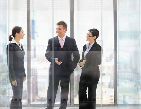 Three happy businesspeople standing in front of office windows, talking and smiling. photo