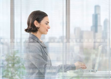 Young businesswoman sitting at desk in modern office behind glass wall, using laptop computer, smiling. photo