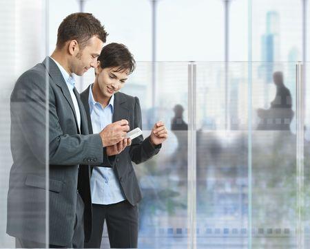 dos personas conversando: Dos empresarios de pie en la oficina moderna, con paredes de vidrio, mirando al tel�fono m�vil inteligente.