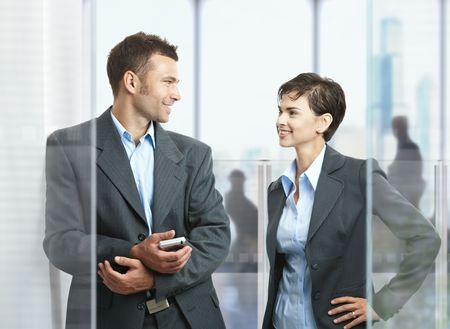 Two businesspeople standing in modern office with glass walls, looking at each other, smiling. Stock Photo - 5758855