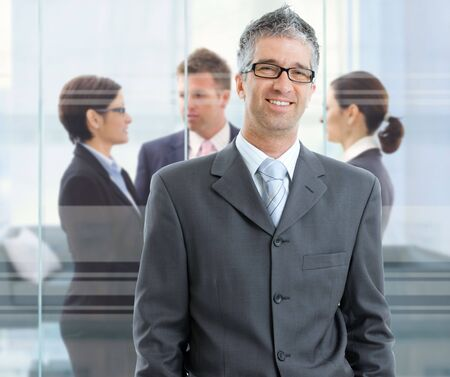 Businessman standing in downtown office, businesspeople talking in background in front of windows. photo