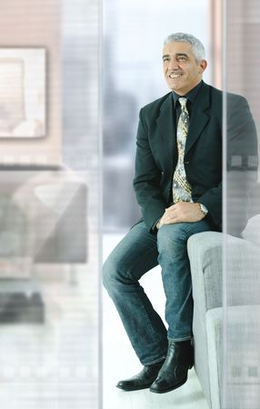 Casual businessman sitting on couch in modern office, smiling. photo