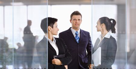 Three young businesspeople standing in modern office talking and smiling. photo