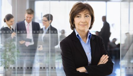 undoubting: Senior businesswoman standing in corporate office,  businesspeople talking in background behind glass wall.