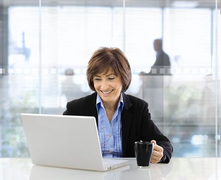 formalwear: Happy senior businesswoman sitting at desk in  modern corporate office, using laptop and drinking coffee. Stock Photo