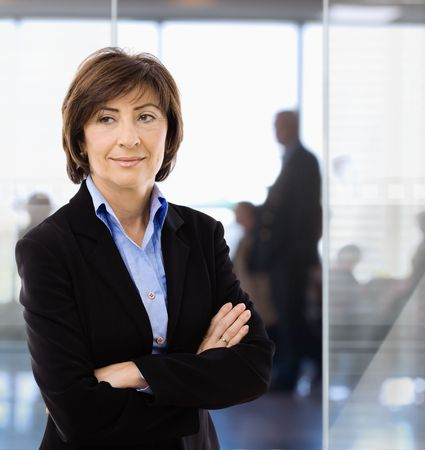 undoubting: Senior businesswoman standing arms crossed in modern corporate office. Stock Photo