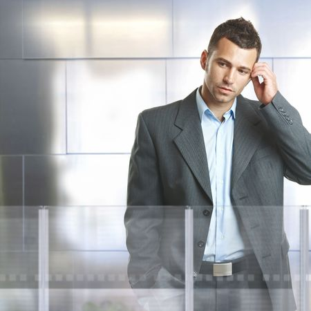 Worried businessman standing in modern office with glass and metal walls. photo