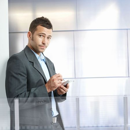 Serious businessman standing in modern office with glass and metal walls, using smart phone. photo