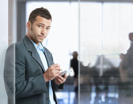 office wear: Serious businessman standing in office lobby , using smart phone, looking at camera.