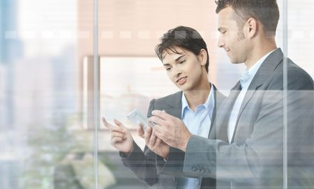 Two businesspeople standing in modern office behind glass wall, using smart mobile phone. photo