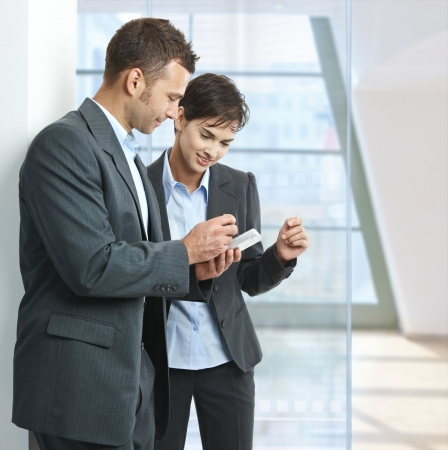 Two businesspeople standing in office lobby , looking at smart mobile phone, smiling. photo