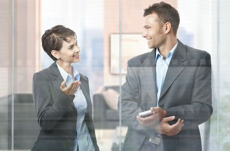 Two happy businesspeople standing in modern office with glass walls, looking at each other, smiling. photo