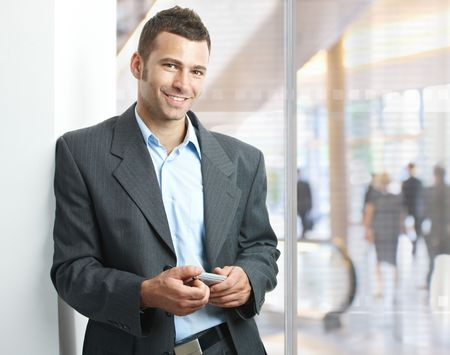 handheld device: Young businessman standing in office lobby, using smartphone, smiling. Stock Photo