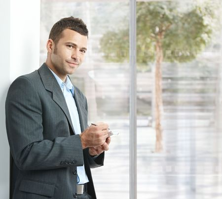 Young businessman standing in office lobby, using smartphone, smiling. Stock Photo - 5758699