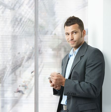 office wear: Young businessman standing in office lobby, using smartphone, smiling. Stock Photo