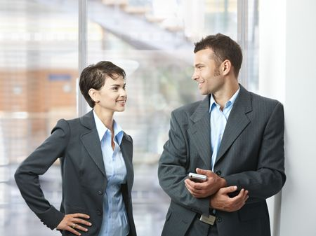 Two happy businesspeople talking in office lobby, looking at each other, smiling. Stock Photo - 5758861