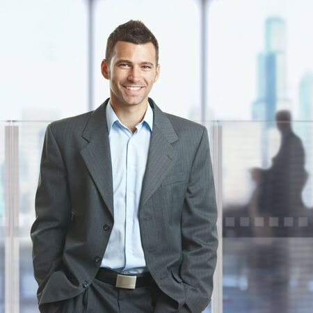 Casual businessman standing with hands in pocket in corporate office lobby, smiling. photo