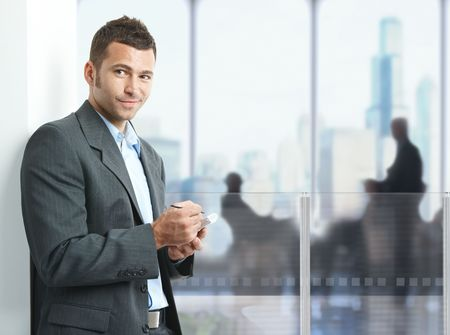 Young businessman standing in office lobby, using smartphone, smiling. photo