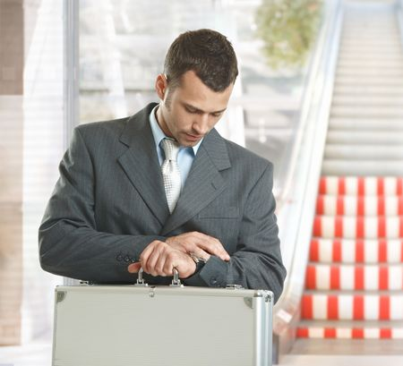 Businessman standing in office lobby looking at his watch, checking time. photo