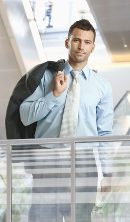 Casual businessman standing in corporate office lobby, holding suitcase. photo