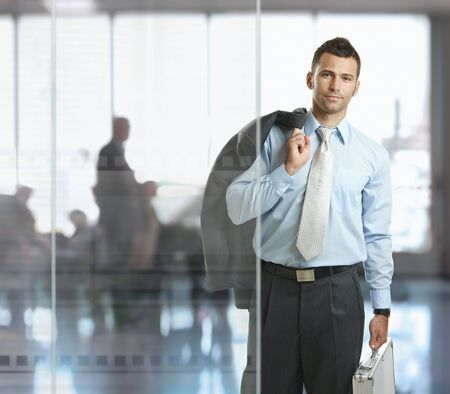 going: Casual businessman leaving office lobby, carrying suitcase. Stock Photo