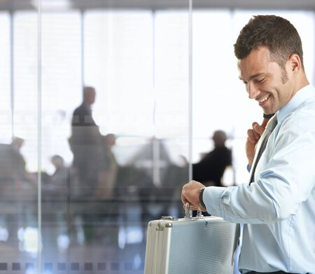 Businessman standing in office lobby looking at his watch, smiling. photo
