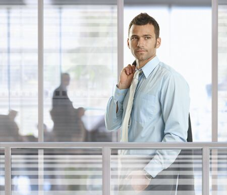 Casual businessman standing in front of glass walls in office, smiling. photo